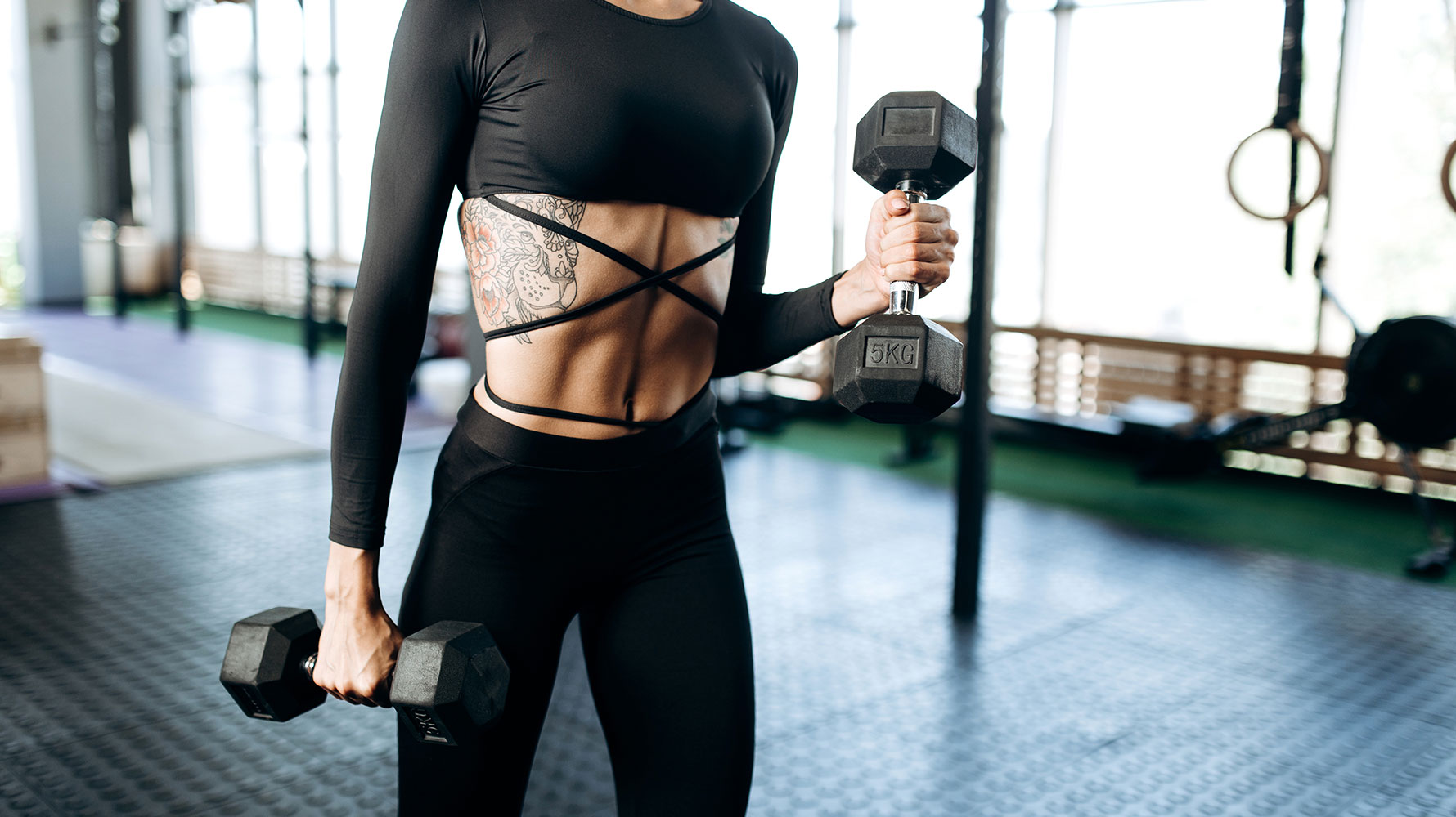performing shrugs with dumbbells